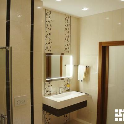 Умывальная зона ванной выделена декоративной плиткой; зеркало подсвечено