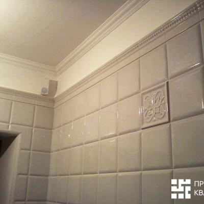 Прачечная выложена керамической выпуклой плиткой, окно обведено керамическим бордюром