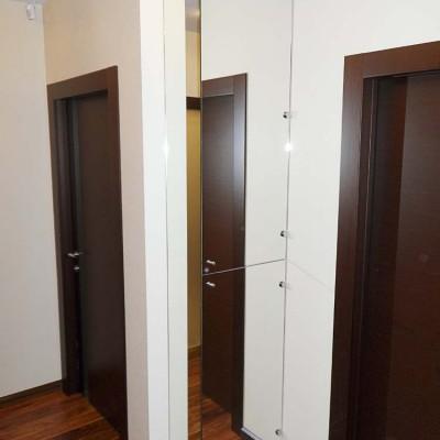 Зеркальный короб в коридоре. В верхней части спрятаны электрощиток и слаботочные провода. В нижней части - шкаф с полками