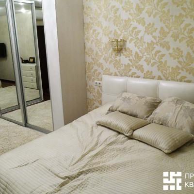 Спальня. Стена за кроватью оклеена виниловыми обоями с классическим рисунком; остальные стены однотонные