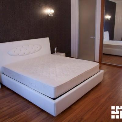 Стена за кроватью выделена контрастными обоями. Слева от зеркального шкафа-купе - дверь в ванную комнату
