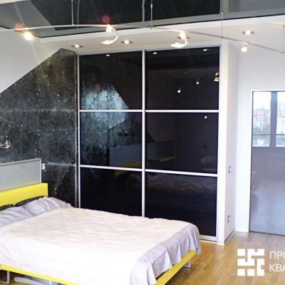 Ремонт квартиры на Дрезденской. Комната сына. В центре шкаф-купе с дверцами из черного пластика. Часть стены обшита клепанными листами металла