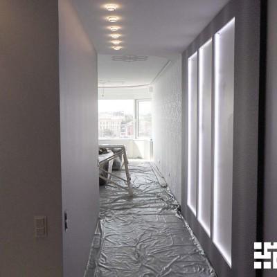 Коридор, вид из прихожей на кухню. Справа стена из ГКЛ с подсвеченными нишами