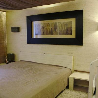 Стены спальни выровняли; на стене возле кровати сделали шумоизоляцию