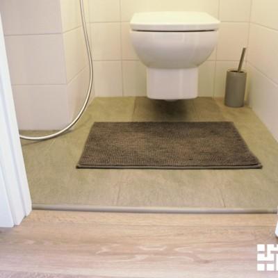 Вход из коридора в туалет. Порожек. По неясным причинам, дом был сдан с уровнем пола в ванной и туалете на 1-2см выше, чем в остальной квартире
