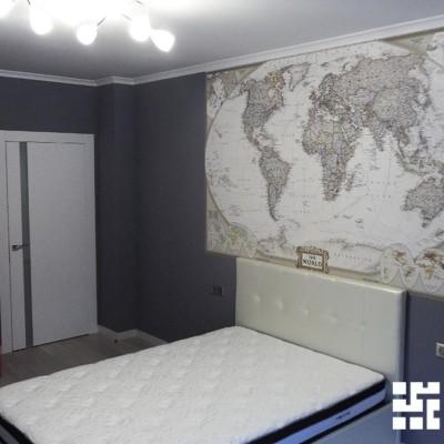 В комнату сына привнесли элементы британского стиля с помощью шкафа-телефонной будки и эффектной карты мира над изголовьем кровати