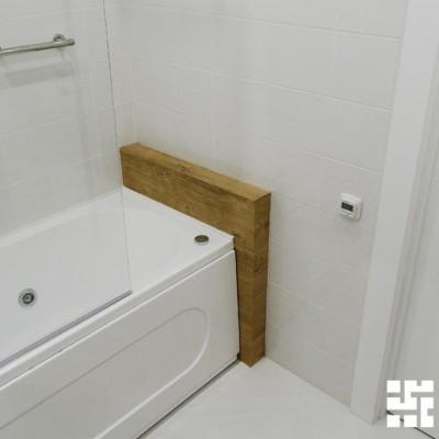 Длина ванны немного короче длины помещения. Полка из гипрока, отделанная плиткой с имитацией дерева, заполняет промежуток и украшает ванную